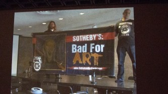 A screen showing two people holding a Sotherbys Bad for Art banner