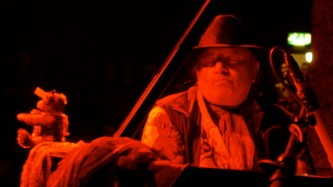 Charlemagne Palestine seated at the piano in red light