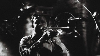 Dave Dove blows into a trombone at INSTAL 05