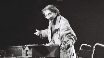 Henri Chopin smiles above a tape recorder