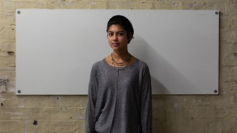 Nisha stands against a white wall, they are wearing a grey jumper