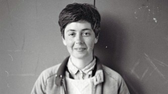 A portrait of Emma Hedditch in front of a grey wall