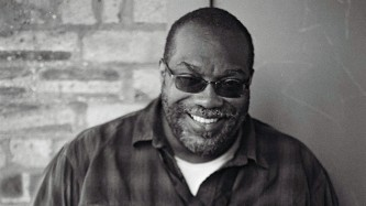 A portrait of Fred Moten wearing sunglasses and a cheeky smile