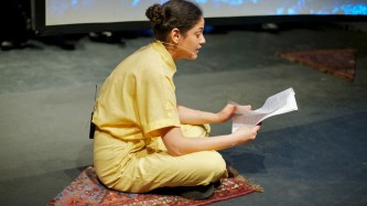 Teresa Maria Diaz Nerio in a yellow jumpsuit reads aloud whist crossed leggedged