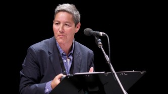 Jack Halberstam in a suit giving a lecture at a microphone