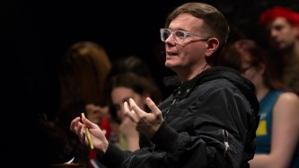 Eric Stanley wearing glasses and a black jacket gesticulates with open hands