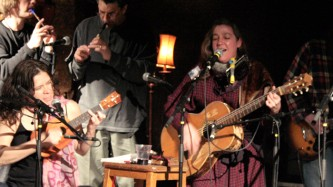 A happy bunch of musicians play guitars, ukelele and whistles