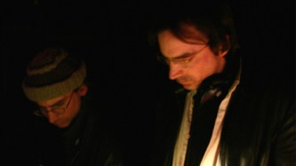 Two Bain brothers look down at a lit mixer in a dark space