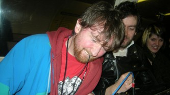 Nackt Insecten wears a blue and red top and chomps on a contact mic in his mouth