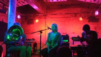 Three performers sit on a red lit stage, a tuba player, a singer and a guitarist
