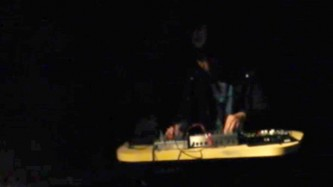 in a dark room Karen Constance plays a mixer on a yellow table