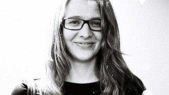 Heather Leigh Murray with glasses and long hair smiles at the camera