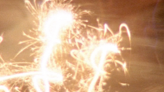 Film still of lit sparklers in close up
