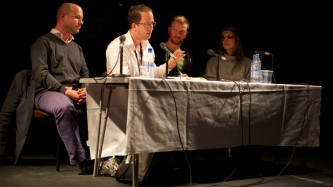 At a panel of four people, a man in a white shirt speaks into a microphone