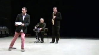 Diego Chamy in slides across the floor behind him a sax player and drummer play