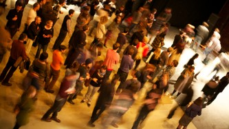 A crowd of people are blurred as they mingle on a grey floor, taken from above