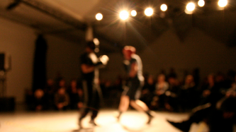 Two figures boxing in front of an audience