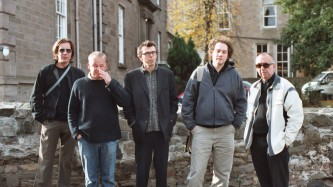 A group of five people stand in a line facing the camera