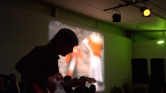 Guitar player silhouetted against projection of a film