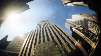 a fisheye lens looks up a blue sky with skyscrapers towering around