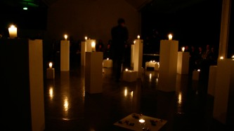 Many plinths with candles on top in a dark space