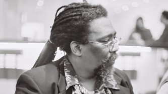 Sabir Mateen in profile wears glasses and dreaded hair and a suit jacket