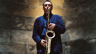 John butcher Plays saxophone direct to camera in front of a stone wall