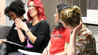 Four People sitting in a row, one in red hair talking
