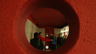 Denis Wood talking to an audience seen through the aperture of an orange hole