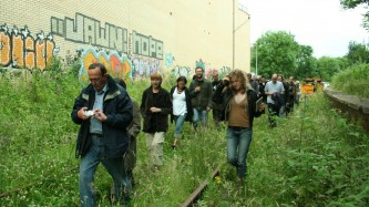 Audience members walking along a railway lined with trees and flowers