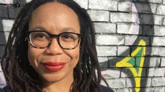 Akwugo with red lipstick and glasses smiles to camera in front of a tiled wall