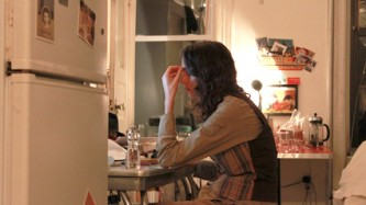 Ayreen Anastas seated at a kitchen table in the evening