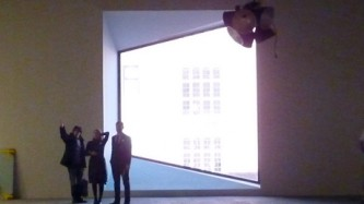 Three figures are silhouetted by a large window in the shape of a parallelogram