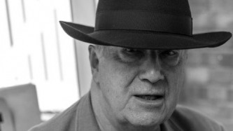 A close up, black & white portrait of John Tilbury, in a large fedora hat