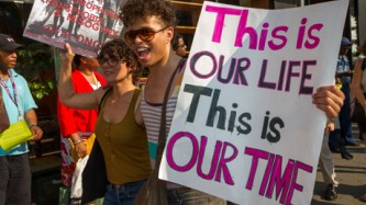 """Reina smiles as they hold a placard: """"This is our life, this is our time"""""""