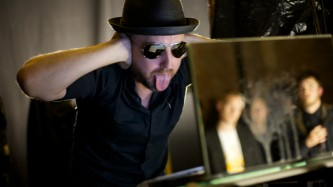 a man in a hat and sunglasses sticking his tongue out