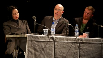 Mark Sanders sitting in middle of two other people at a panel discussion