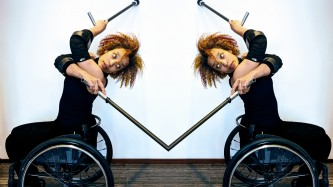 Seated in her wheelchair, Alice Sheppard, crosses her crutches behind her