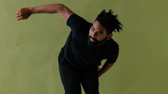 Jerron crouches to one side, right arm extended, infront of a green background
