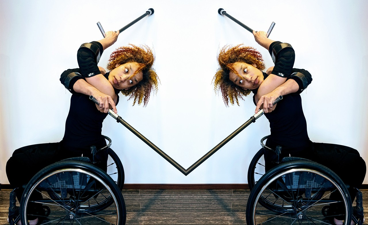 Seated in her wheelchair, Alice Sheppard, crosses her crutches in front of her